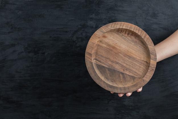 Segurando uma placa redonda de madeira em fundo preto