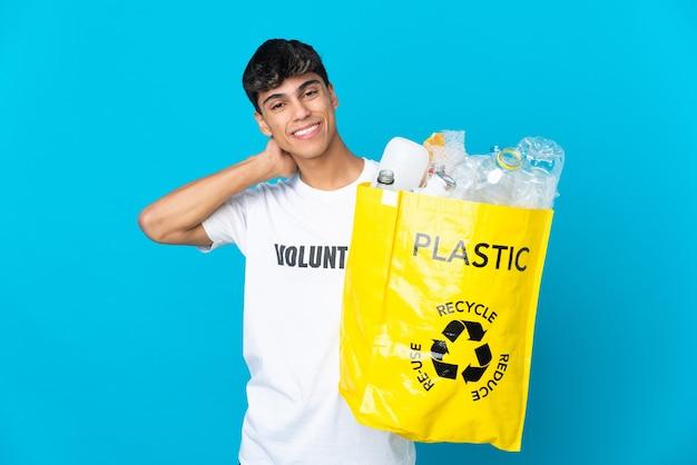 Segurando uma sacola cheia de garrafas plásticas para reciclar e rindo