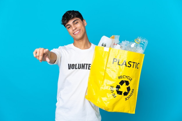 Segurando uma sacola cheia de garrafas plásticas para reciclar sobre o azul apontando para a frente com expressão feliz