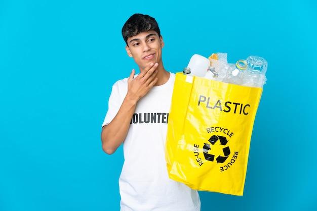 Segurando uma sacola cheia de garrafas plásticas para reciclar sobre o azul olhando para cima enquanto sorri