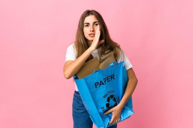 Segurando uma sacola cheia de papel para reciclar sobre algo sussurrando rosa