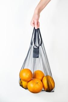 Segurando uma sacola reutilizável cheia de laranjas.