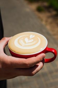 Segurando uma xícara de café cappuccino vermelha recém-feita à luz do sol