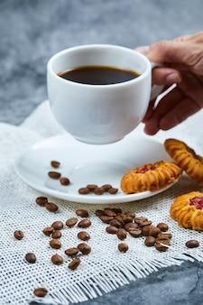 Segurando uma xícara de café com biscoitos e grãos de café.