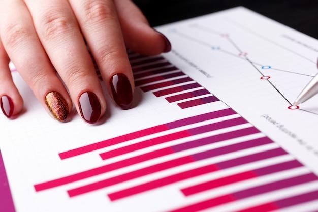 Segurar o braço feminino e apontar caneta prata no gráfico financeiro