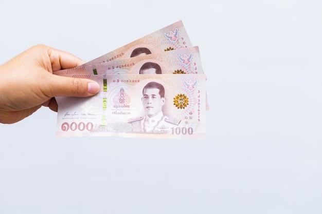 Segure notas iguais a três mil baht tailandês.