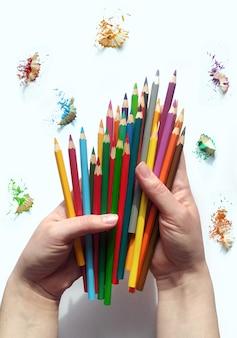 Segure o lápis de cor nas mãos. lápis aquarela de arco-íris em fundo branco.