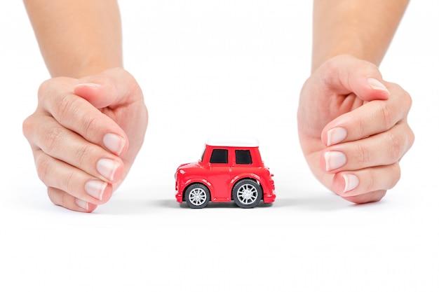 Seguro de automóvel. miniatura de carro coberto pelas mãos.