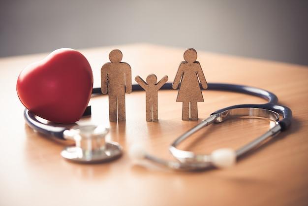 Seguro médico com família e estetoscópio na mesa de madeira