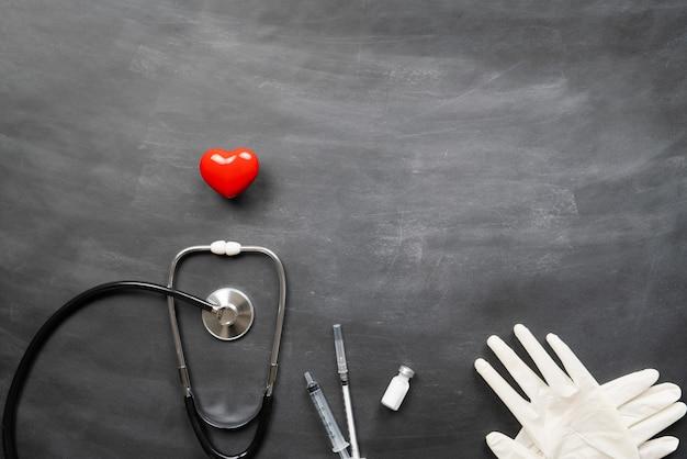 Seguro médico de saúde com coração vermelho, estetoscópio e suprimentos médicos