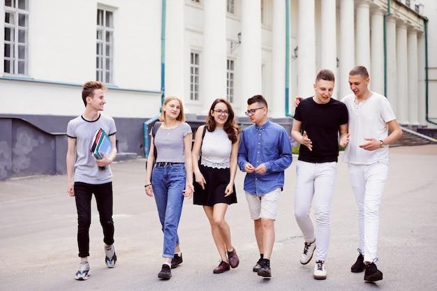 Seis alunos amigáveis caminham perto do prédio da universidade depois das aulas, sorrindo, aproveitando o tempo livre