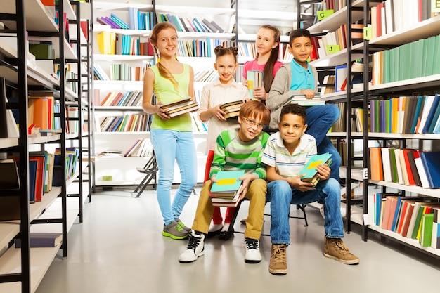 Seis alunos juntos na biblioteca com pilhas de livros