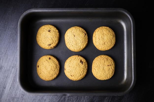 Seis biscoitos assados redondos em uma assadeira preta, vista de cima