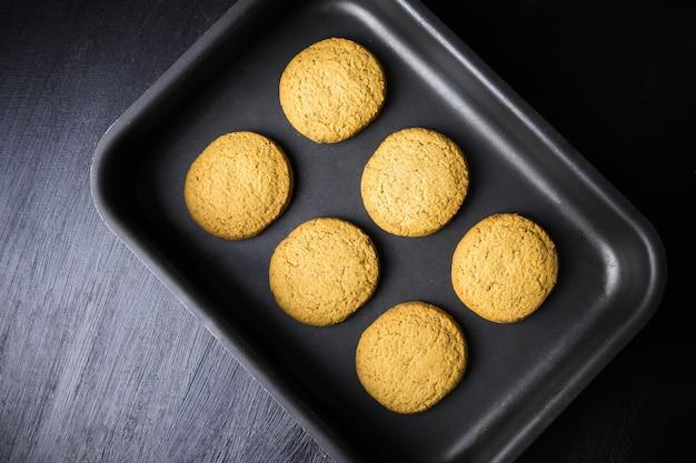 Seis biscoitos assados redondos na assadeira preta, vista de cima