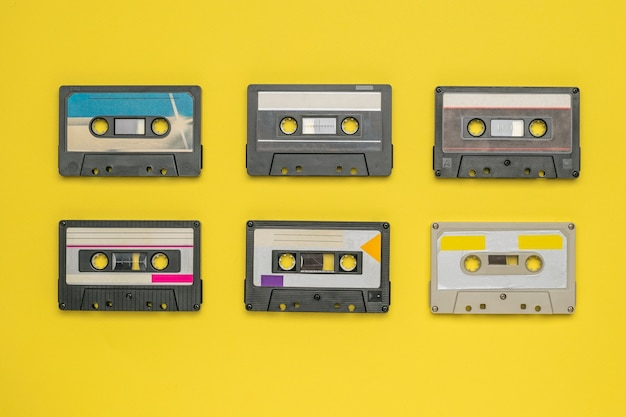 Seis cassetes de áudio com fita magnética em uma superfície amarela