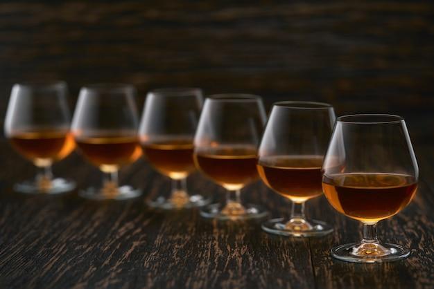 Seis copos de congac em uma mesa preta