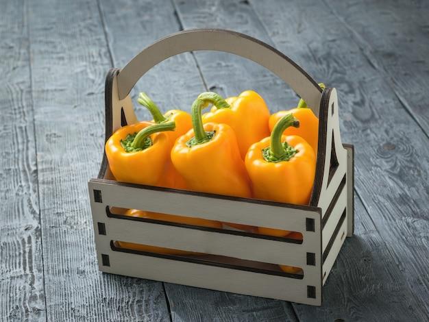 Seis grandes pimentas maduras em uma caixa de madeira sobre uma mesa de madeira. comida vegetariana.