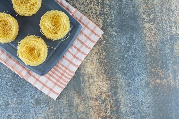 Seis pilhas de espaguetes finos no tabuleiro, na toalha, no fundo de mármore.