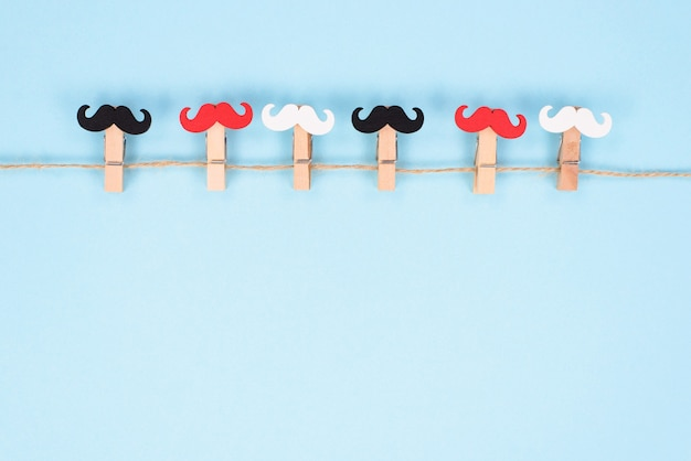Seis prendedores de roupa com bigode de cores diferentes pendurados em uma corda isolada em fundo pastel