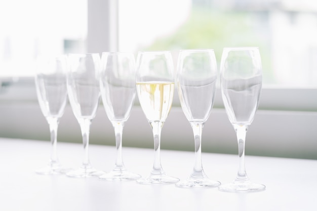 Seis taças de vinho na mesa e apenas 1 com vinho, conceito de diferença