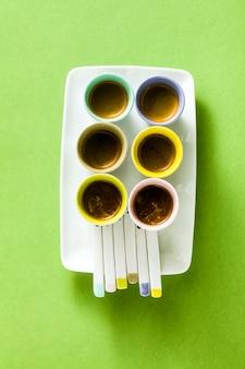 Seis xícaras multicoloridas de café expresso italiano com colheres de porcelana em um prato de servir, sobre um fundo verde.