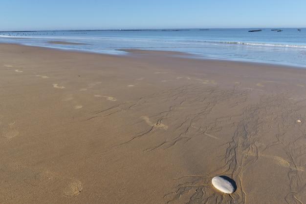 Seixo na areia molhada na praia com o fundo do mar no oceano atlântico, na frança