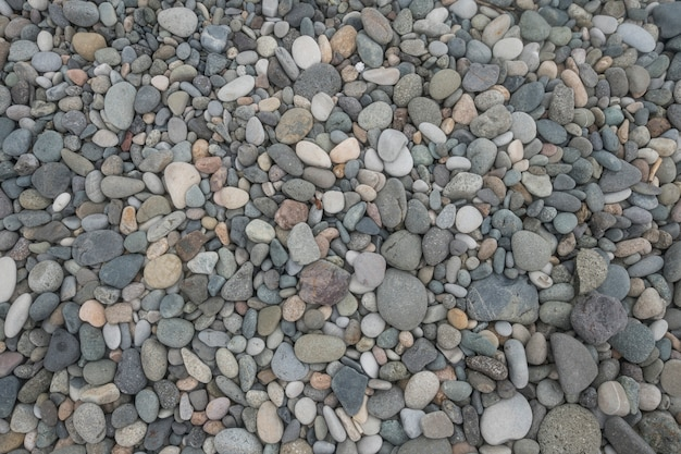 Seixo na praia em fundo de textura abstrata de dia ensolarado