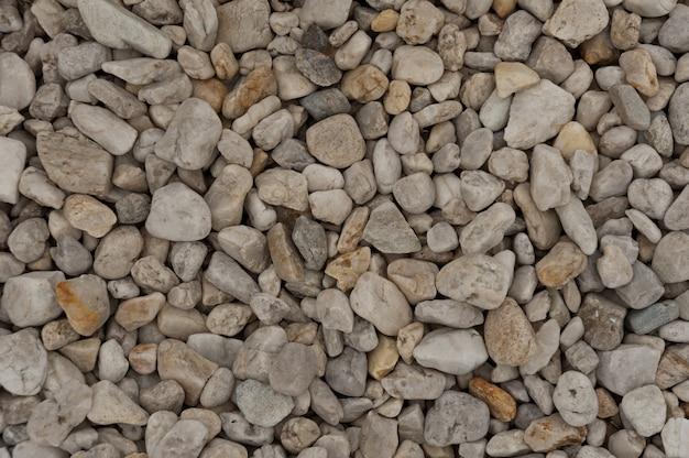 Seixos de pedra marrons e fundo cinzento da textura do cascalho para a decoração.