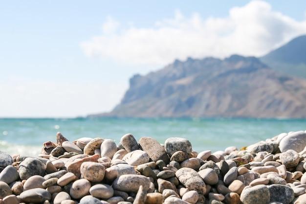 Seixos do mar contra as montanhas borradas e o mar