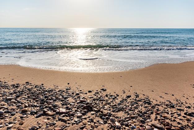 Seixos do mar na costa ao nascer do sol com o fundo do mar desfocado