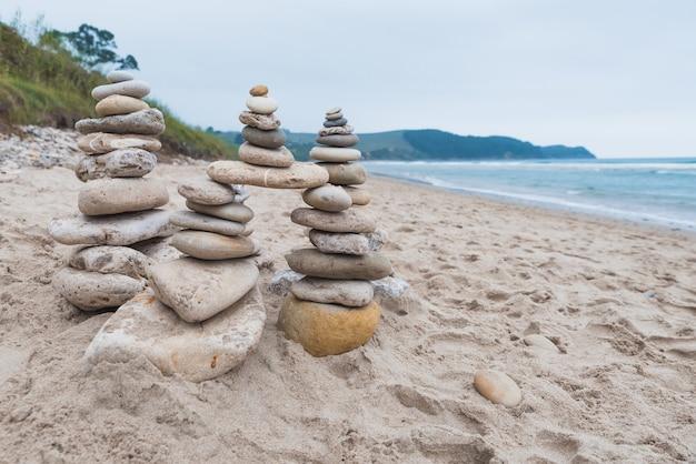 Seixos empilhados uns sobre os outros em equilíbrio na praia