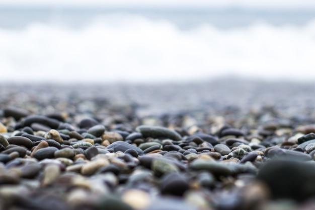 Seixos molhados do mar com uma onda após uma tempestade com uma profundidade de campo rasa