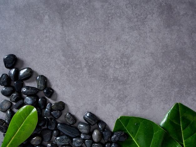 Seixos pretos e folhas no fundo de mármore cinza.
