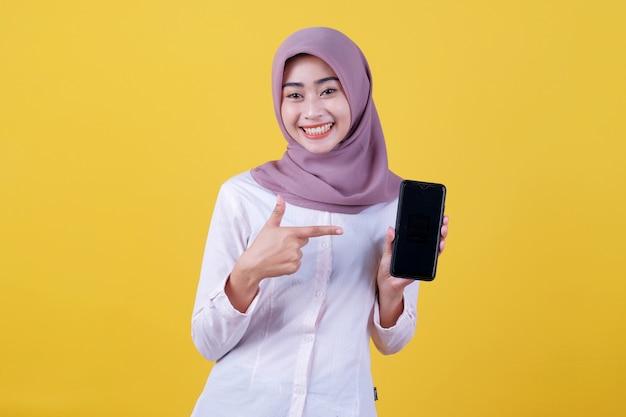 Seja esperto, compre este dispositivo, retrato de uma jovem mulher asiática rindo alto, usando um hijab apontando para o smartphone, mostrando a tela do dispositivo