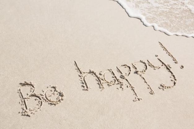 Seja feliz escrito na areia