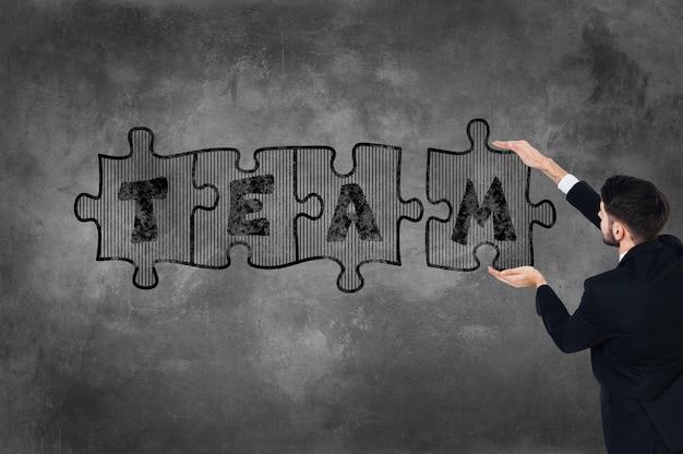 Seja o time! vista traseira de um jovem de terno completo tocando a parede de concreto