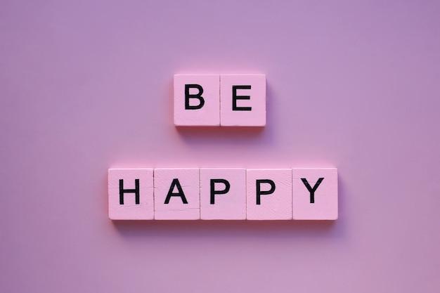 Seja palavras felizes em uma superfície rosa