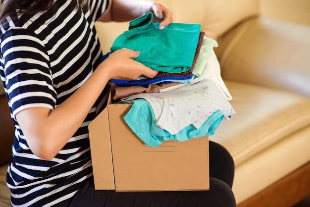 Seja voluntário com doações para pessoas pobres. caixa de papelão com roupas para caridade.