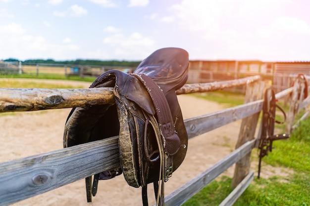 Sela de cavalo pendurada em uma cerca, close-up