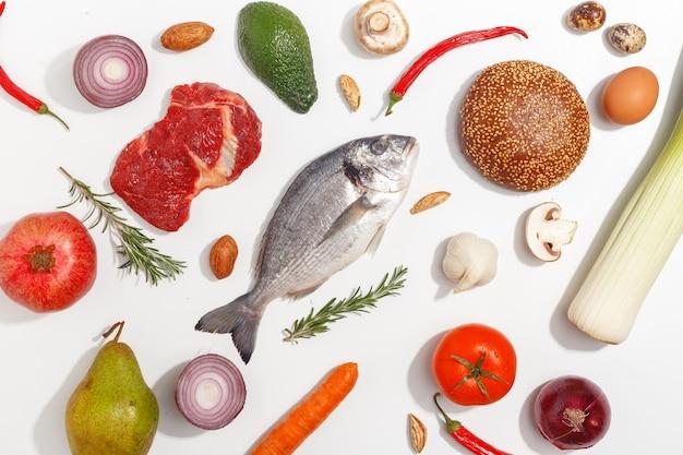 Seleção comer limpo do alimento saudável: fruto, vegetal, sementes, peixe, carne, legume de folha no fundo branco. vista do topo.