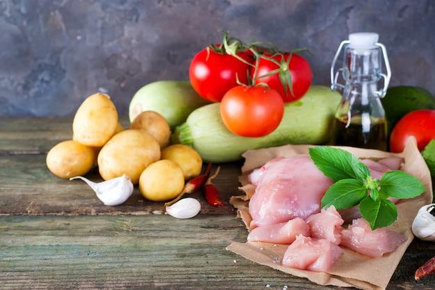 Seleção da carne crua da galinha com os vegetais na placa de madeira proteínas magras.
