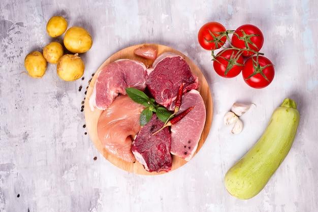 Seleção da carne crua diferente com os vegetais na placa de madeira. proteínas magras.