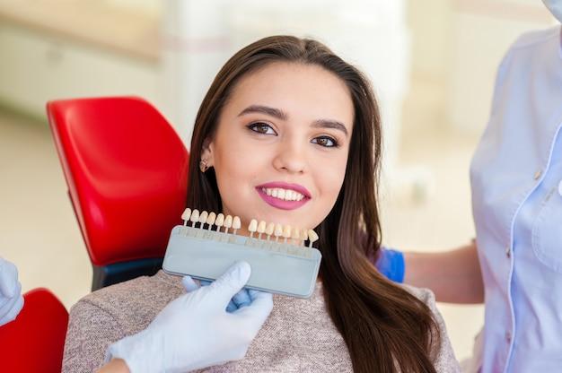 Seleção da cor dos dentes para uma bela mulher da odontologia