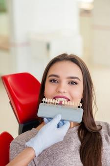 Seleção da cor dos dentes para uma linda garota em odontologia.