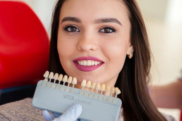 Seleção da cor dos dentes para uma menina bonita em odontologia.