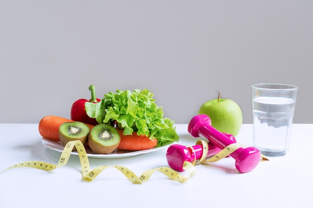 Seleção de alimentos saudáveis com frutas, vegetais e item para perder peso no fundo da mesa branca