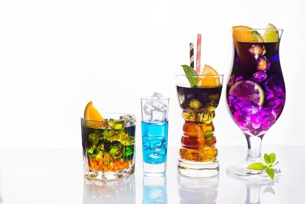 Seleção de bebidas festivas coloridas, bebidas alcoólicas e cocktails em copos elegantes em branco