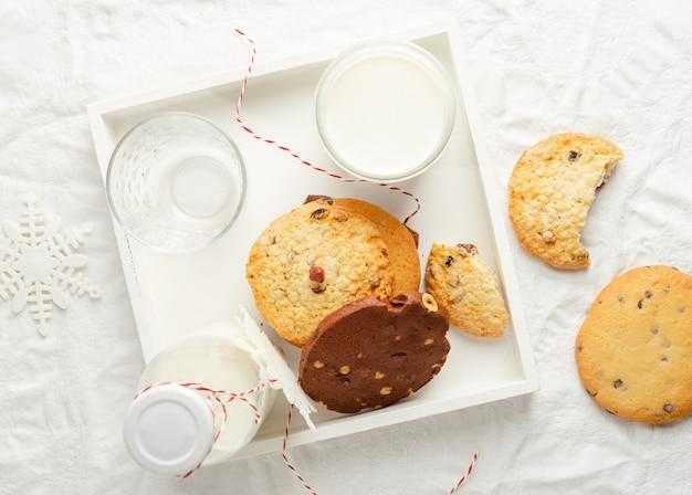 Seleção de biscoitos caseiros e leite na bandeja de madeira