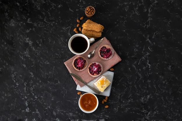Seleção de bolos doces, cupcake e cheesecake, café quente em cima da mesa, nozes amêndoas em uma tigela