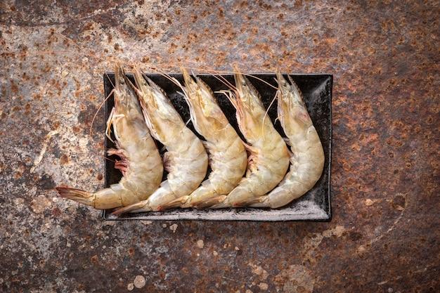 Seleção de camarão branco fresco cru em placa de cerâmica retangular preta sobre fundo de textura enferrujada, vista de cima, camarão de perna branca